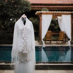 Selecting a wedding dress is more than just a fitting.... It's process - a memory in the making -OCJ-Niatnya mau sewa aja buat wedding dress aku.. Tapi liat biaya sewa kok kayanya sayang banget uang segitu gede buat nyewa baju doang wkwkwkwkw *maklum pengantennya PUWEEELIIIT* Dan rata2 wedding dress yg aku mau yang simple2 itu harga sewanya lebih mehong dari yang ribet n rame 😅😅 akhirnya dengan berbagai pertimbangan, kuputuskan untuk buat wedding dress sendiri, yg sesuai sama mau aku. Yang simple ga ribet tapi tetep cantik n anggun.. Dan biayanya jauh lebih murah dr aku sewa PLUS bajunya jadi hak milik 🤑🙃 Seperti yang kalian ketahui bahwa aku mengurus semua keperluan pernikahanku ini sendiri. Jadi every detail dari bahan2nya aku yang pergi dan cari sendiri, bahkan beads yang terpasang dan beli dimana aku ikut mikirin. Dan semuanya ini ga mungkin terwujud tanpa tangan berbakat @risnayustiani , my wedding dress maker 💕 sempet ada drama diawal pembuatan krn tetiba Risna mau quit from this job bcause she's pregnant.. Tapi akhirnya ga jadi karena satu dan lain hal 😘😘 Aku gapernah dibuat kecewa sama Risna dari awal aku buat horden wkwkwkwwkwk trus baju lamaran dan sampai pada akhirnya 2baju pernikahanku. Untuk akad dress aku pengen pake baju kurung melayu. Kenapa ? Karena aku suka kesimple an baju pengantin melayu saat menikah. Dan aku pengen banget pake salah satu koleksinya @iam_inderaloka , tapi sayang jauh yaa booo'.. aku bukan anak sultan juga 🤣 jadi aku ambil inspirasi wedding dress aku dr sana. Terus biar ga menghilangkan ciri khas Indonya, aku pengen atasannya ala2 kebaya kutubaru gt. Aku gamau buat baju yang ribet karena aku pengen memudahkan dress maker aku juga.Baju kedua adalah baju ide2an kita berdua. Karena aku ga mau ganti baju sampe 3x.. akhirnya aku sama Risna buat Party Dress yang lain dari biasanya 🤣🤣🤣 kita buat 2 looks dalam satu baju.. And it works guys~ untuk foto yang kalian lihat itu adalah 1st look dr dressnya yang aku gunakan saat Wedding Enteran