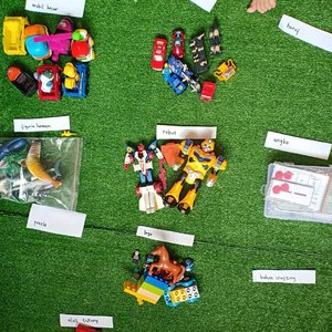 """Menata MainanPojok bermain SID yaa gitu deh campur aduk. Banyak mainan yang jarang ia mainkan.Polanya, makin berantakan, SID makin ga betah main di sana.So, saya kelompokkan mainan menjadi beberapa kategori seperti lego, mobil kecil, mobil besar, LaQ, magnet, alat berhitung, alat membaca, robot, juga senjata 🔫Tiap mainan dibungkus sesuai kategori. Simpan pakai plastik ziplock, toples bekas, kontainer kecil, besek, atau wadah lain yg ada di rumah. Tahan godaan beli wadah baru 😝Trus, mainan ini disimpan di kotak mainan besar. Mainan yang dipakai aja yang diletakkan di rak bermain. Setiap minggu ada rolling mainan jadi serasa punya mainan baru ~Trussss apa selalu rapi?Enggak, lah. Namanya juga bermain. Selesai main, udah capek beresin.Tapi ... dengan setiap mainan udah punya """"rumah"""" jadi lebih mudah merapikan kembali ke rumah masing-masing.Yaaa mainan juga #stayathome alias #dirumahaja#helenamantrastory #idemain #idebermain #diytoys #homeschooler #homeschooling #homeeducation #zerowaste #gogreen #diycardboard #playideas #teachermum #playandlearn #recycleandplay #recycletoys #recycled #sekolahalamsemesta #clozetteID #konmari #konmarimethod #berbenah #gemarapi #toys #diytoys #sewamainan #sewamainanjakarta #toysrental #toysrentaljakarta"""