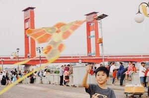 This boy and his kite. His very first experience play with kite. . Sebagaimana anak Jakarta yang jarang beraktifitas di luar ruangan kecuali renang dan main bola di sekolahan, Vio belum pernah main layangan. Pas kemaren jalan ke BKB liat ada tukang jual layangan, dia pengen. Ya udah lah ya dibeliin. Ga mahal ini. 😂 Lalu heboh lah anaknya main layangan. 😂 . The other side of the story, lapak yang jual layangan ini tadinya sepi. Ga ada yang beli. Noleh juga ngga ke bapak yang jualannya. Tapi gara-gara Vio mainnya heboh dan seru sendiri, lalu mendadak bapaknya diserbu pembeli. Lumayan lah lalu 5 layangan lagi setelah Vio beli. 😂 Lalu mendadak banyak layangan di udara dan bocahnya senang karena sudah memberikan rejeki buat Bapak jual layangan. 😆 . . . . . #boy #kids #kiddos #kite #play #afternoon #ampera #bridge #palembang #travel #travelgram #instatravel #blogger #sonyalpha #vsco #whpcolorplay #whpontheroad #clozetteid #instadaily #instagood