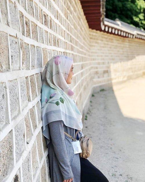 """Pose nyender tembok di gerbang Jongmyo Shrine sambil mikir : """"Duh tadi sehabis ambil topi anak - anak, kopernya udah digembok belum ya? """"...Menikmati hari pertama di Seoul dengan jilbab segi empat dari @rj_indonesia yang dipadukan dengan outer dari @id_theexecutive . Seoul hari pertama cukup terik namun berangin. Paduan pakaian ini cocok sekali untuk dikenakan. Jilbab RJ Signature ini lebarnya cocok banget untuk menutup dada dan punggung. Motif bunganya pun cantik, jadi berasa ikutan cantik 🤪...#buyutravelling #jongmyoshrine #rjindonesia #hijab #wheninseoul #clozetteid"""